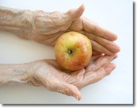 Older hands holding an apple